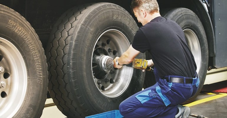 Man changing truck tyre