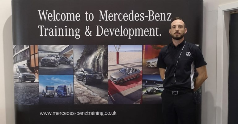 Mercedes trainer standing in front of Welcome to Mercedes-Benz Training and Development sign