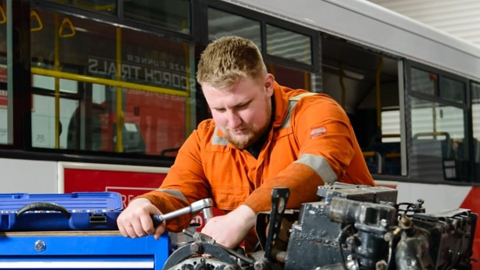 apprentice working on bus engine