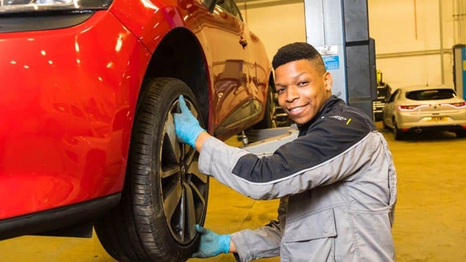 apprentice holding car tyre