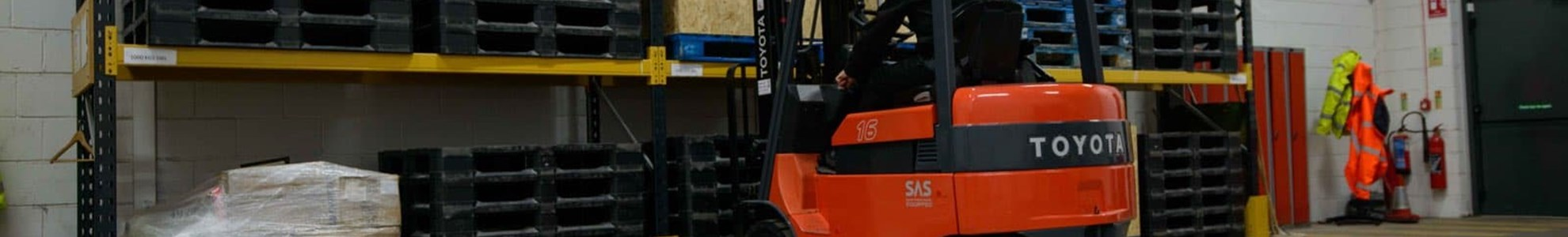 forklift stacking pallets in a rack
