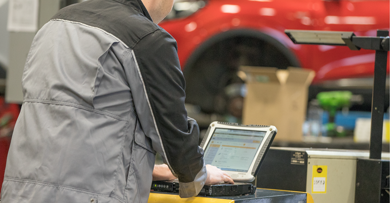 Technician looking at laptop running an MOT